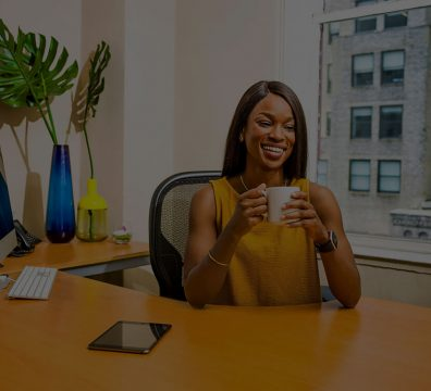 Smiling Black woman wearing gold top sitting at an office desk and drinking from a mug