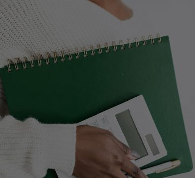 Close up of a Black woman's hands while holding a green notebook, white calculator and white pen