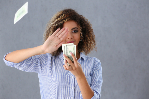 Black woman with blonde curls holding a stack of cash