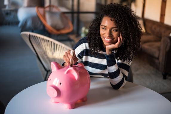 Black woman with dark curls saving money using a pink piggy bank