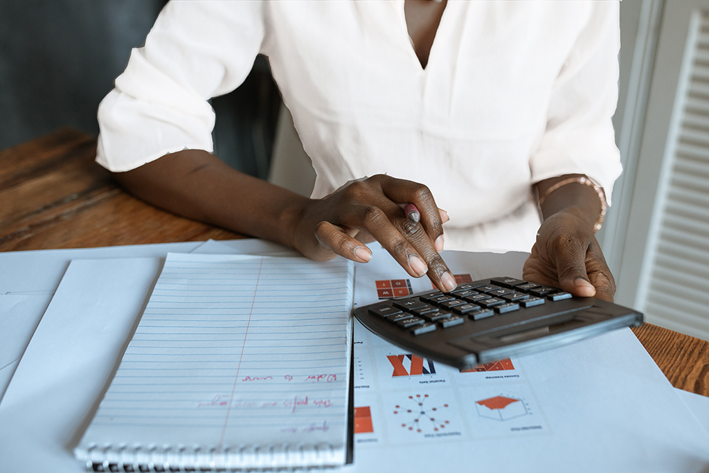 Close up of a Black woman's hands using a calculator and taking notes on a white notepad