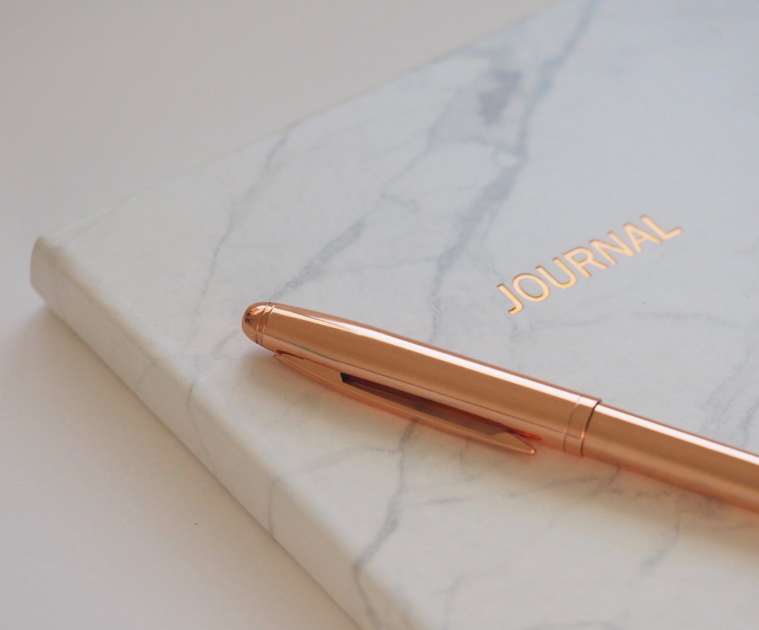 A journal with a marbel cover and rose gold pen