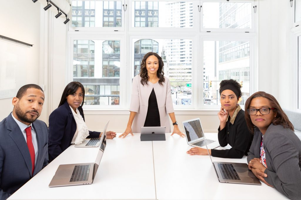 Black woman and professional team at an office in front of a window